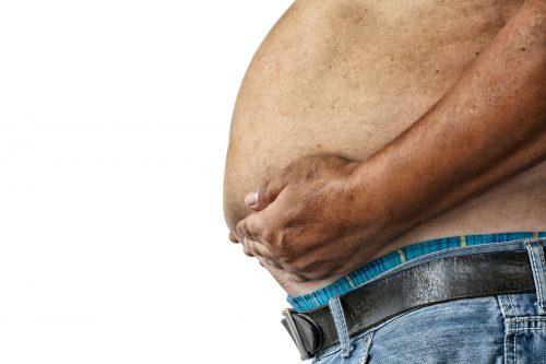 אדם שמן מחזיק את כרסו