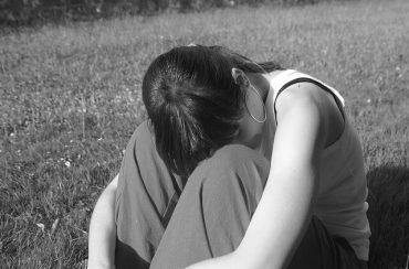 אישה עצובה מניחה ראשה על הברכיים